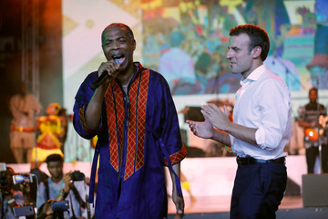 French President Emmanuel Macron stands on stage as Nigerian musician Femi Kuti performs during Macron's visit to the Afrika Shrine nightclub in Nigeria's commercial capital Lagos