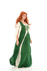 full length portrait of red haired girl wearing long green medieval gown. standing pose, isolated on white studio background.