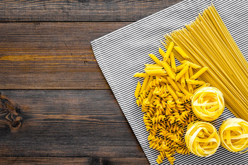 Assortment of raw pasta. Spaghetti, fusilli, penne, fettuccine on blue tablecloth on dark wooden background top view copy space