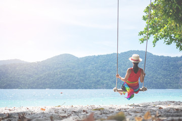 Outdoors lifestyle fashion portrait stunning young girl enjoying on swing on the tropical island. In the background the sea. Wearing stylish dress.