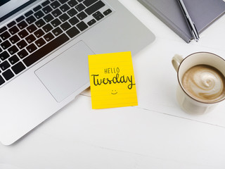 Hello Tuesday text on sticky note on work desk