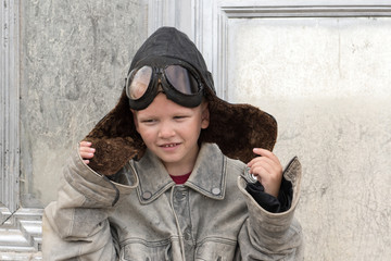 Funny child with independent character wore leather flying hat, pilot's glasses, jacket. Boy dreams of traveling, flying on airplanes, victories, adventures. Concept of man's education, patriotizm