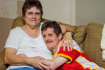 Man With Downs Syndrome Hugs His Older Sister On A Couch