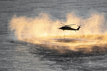 Up close shot of helicopter performing training rescue operation over the columbia river at sunset. Water splashes, vapor and sprays rise from the river surface. Rope hangs from the helicopter.