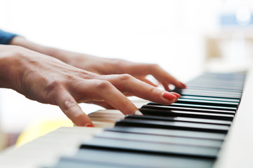 Close up of pianists hand playing piano. Shallow deep of field.