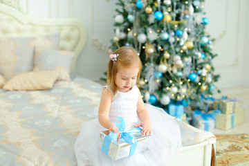 Little caucasian girl sitting on bed with present and wearing white dress, decorated fir tree in background. Concept of winter holidays and New Year gifts.