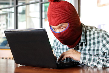 Masked hacker wearing a balaclava stealing importance data from laptop. Internet crime concept. - fototapety na wymiar
