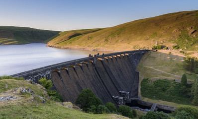 Claerwen Reservoir and dam, in the Elan Valley, mid Wales. The sun is setting and the sky is beginning to turn a deep blue