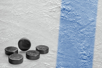 Hockey pucks and a fragment of the ice arena with a blue line