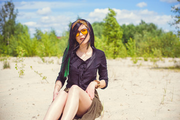 Young hipster woman posing at sand in hippie style and accessory. boho traveler girl in gypsy look. summer travel. atmospheric movement and sensual portrait with green locks