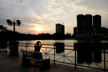 A man takes a photo during sunset at a residential property development by Agile Property in Zhongshan