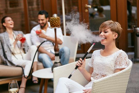 People Smoking Shisha, Drinking Cocktails In Hookah Bar
