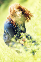 Beautiful red-haired woman in a Boeho style dress in a field
