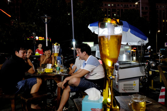 People drink beer at an outdoor market in Zhongshan
