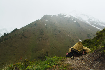 A man in the mountains lying photographing