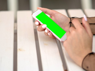 Mockup image of white mobile phone with green screen and hand holding phone