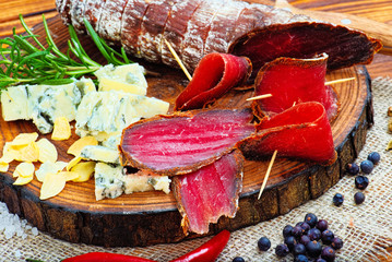 Sliced cured bresaola with spices and a sprig of rosemary.