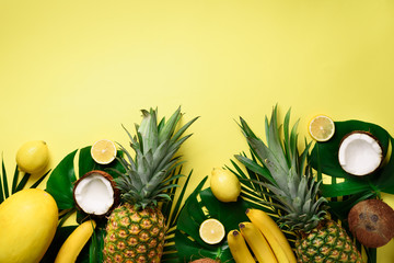 Exotic pineapples, ripe coconuts, banana, melon, lemon, tropical palm and green monstera leaves on yellow background with copyspace. Creative layout. Monochrome summer concept. Flat lay, top view.