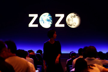 A woman is seen in front of the logo of Zozo, which operates Japan's popular fashion shopping site Zozotown and is officially called Start Today Co, at an event launching the debut of its formal apparel items, in Tokyo