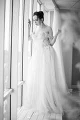 The young beautiful brunette woman in a gorgeous dress standing near the window indoor and looking through it