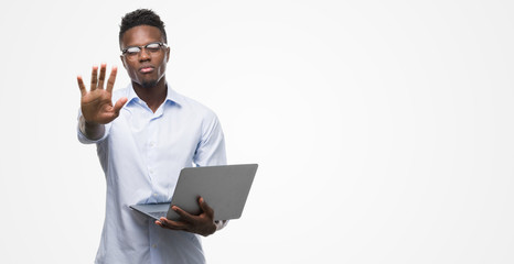 Young african american businessman using computer laptop with open hand doing stop sign with serious and confident expression, defense gesture