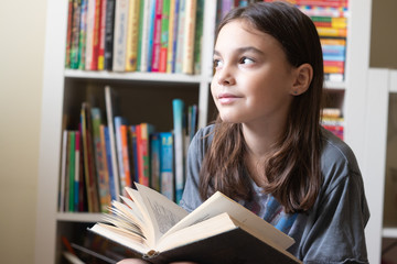 beautiful girl reads a dark book on the background of a bookcase