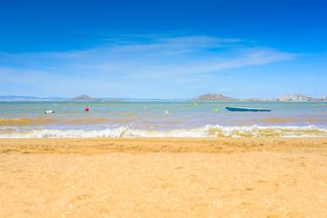 European sandy beach, boat and blue sea.