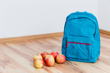 Blue school backpack and apples