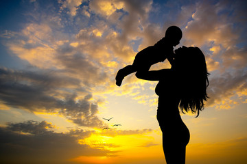 mother with baby at sunset