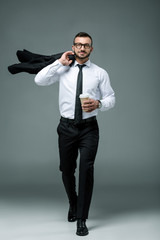 handsome businessman walking with disposable coffee cup on grey