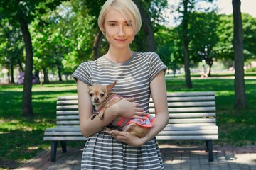 A blonde girl holding a chihuahua in the summer park. The small pet wearing a cute sundress. The toy dog's owner looking at the camera, smile on her face, while carrying her funny four-legged friend.