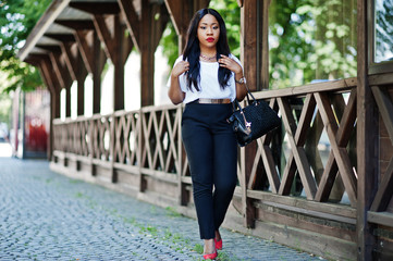Stylish african american business woman with handbag on streets of city.