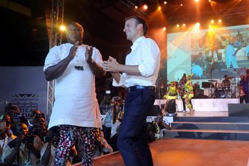 French President Emmanuel Macron dances next to Lagos Governor Akinwunmi Ambode at the Shrine Africa in Lagos