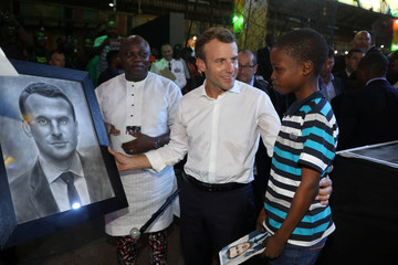 French President Emmanuel Macron meets with a young boy who drew a portrait of him during a visit to the Afrika Shrine in Lagos
