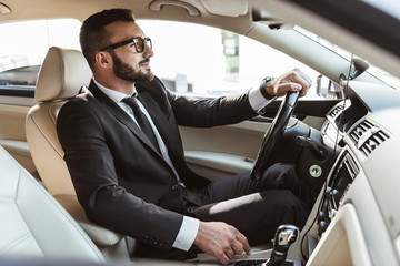 side view of handsome driver in suit driving car Fototapete