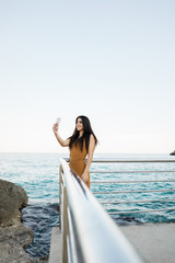 Stylish woman taking selfie on beach