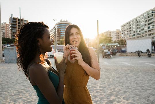 Playful women enjoying drinks on beach