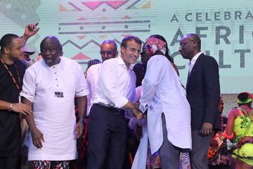French President Emmanuel Macron stands next to Lagos Governor Akinwunmi Ambode at the Afrika Shrine in Lagos