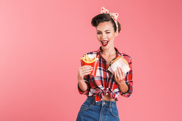 Young pin-up woman holding french fries and burger.