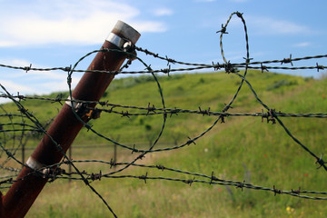Barbed wire on a rusty fence to protect radar antenna in the harbor of Rotterdam.