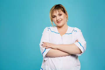 Thee quarter isolated studio portrait of a beautiful chubby woman in a white lab coat. The confident lady posing over the blue background, looking at the camera, smiling. Body positive concept.