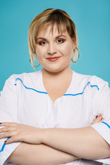 Close up isolated studio portrait of a beautiful overweight woman in a white lab coat. The confident lady posing over the blue background, looking at the camera, smiling. Body positive concept.