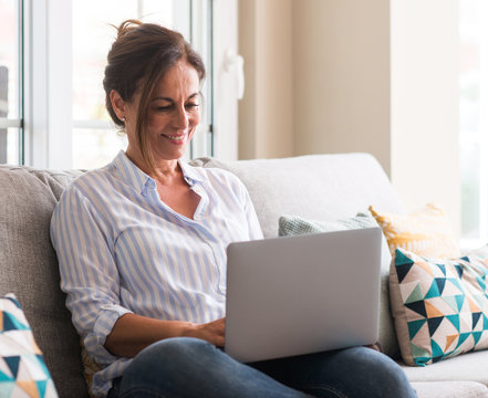 Middle aged woman using laptop in the sofa with a happy face standing and smiling with a confident smile showing teeth