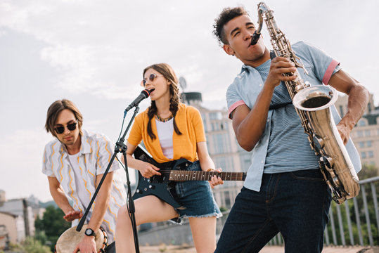 Multiracial young people with guitar, djembe and saxophone performing on street