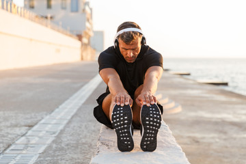 Photo of healthy caucasian man 30s in tracksuit warming up and stretching legs off coast, while listening to music via wireless headphones during sunrise