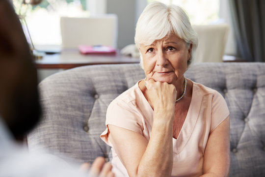 Depressed senior woman having therapy with psychologist