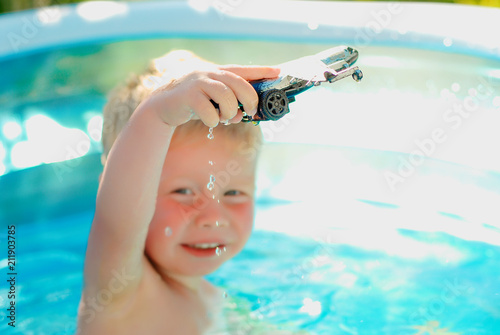 5958a4a7da Baby with toy plane in swimming pool. Little boy learning to swim in outdoor  pool. Swimming with kids. Healthy sport activity for children.