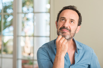 Handsome middle age man serious face thinking about question, very confused idea