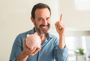 Middle age man save money on piggy bank surprised with an idea or question pointing finger with happy face, number one