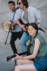 Multiracial young people with guitars and djembe performing on street